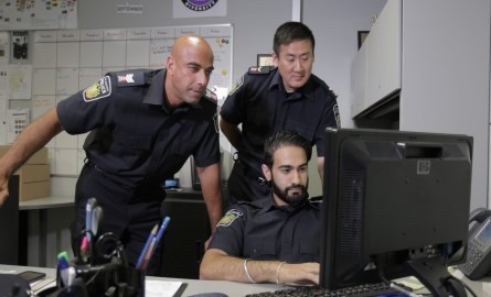 3 Officers looking computer