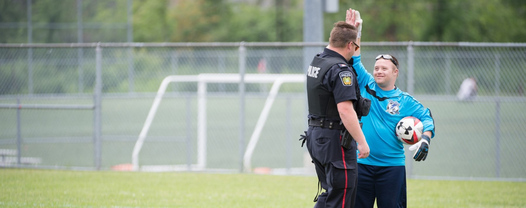 officer giving high five to soccer player