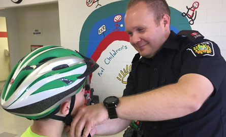 Male employee putting bike helmet onto child